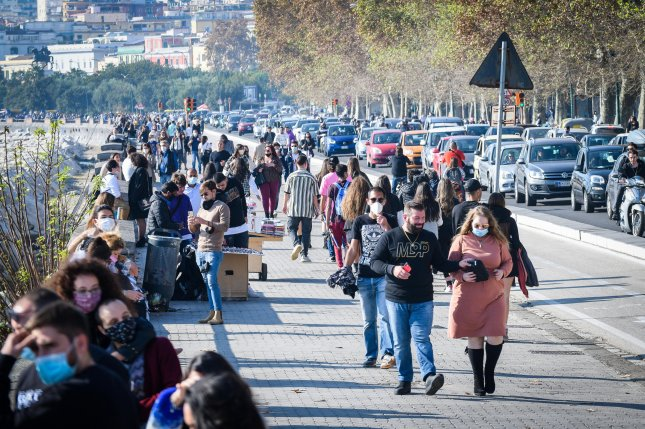 Crowds gather at the seafront of Naplesafter several other regions in Italy entered a partial lockdown on Friday. Naples is under a nationwide curfew. Photo by Cesare Abbate/EPA-EFE