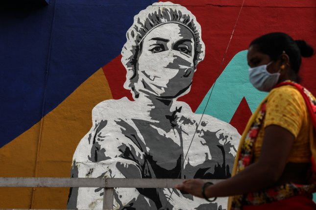 An Indian woman wearing protective face mask walks in front of a graffiti honoring frontline workers in the fight against the spread of coronavirus COVID-19, outside Mahim railway station in Mumbai on Friday. Photo by Divyakant/EPA-EFE