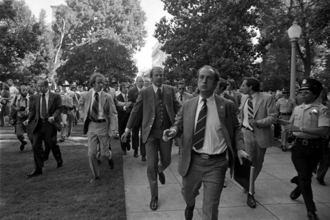 Secret Service agents rush President Gerald R. Ford toward the California State Capitol following an attempt on the president's life by Lynette Squeaky Fromme -- a disciple of Charles Manson -- on September 5, 1975, in Sacramento, Calif. Fromme escaped from prison on December 23, 1987. File Photo courtesy Gerald R. Ford Library