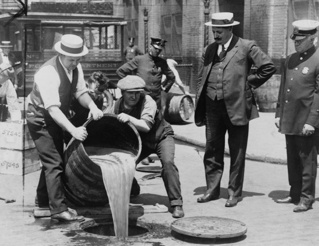New York City Deputy Police Commissioner John A. Leach, right, watching agents pour liquor into sewer following a raid during the height of prohibition. File Photo by Library of Congress/UPI