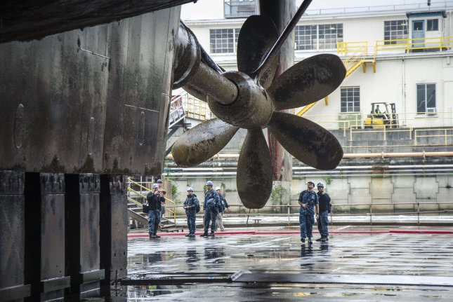 Sailors assigned to the submarine tender USS Frank Cable see their ship's propeller for the first time as she drains in dry-dock, in Portland, Oregon on May 2, 2017. According to the National Trade Council there is only one U.S. company that can repair Navy submarine propellers. Photo by Alana Langdon/U.S. Navy/UPI