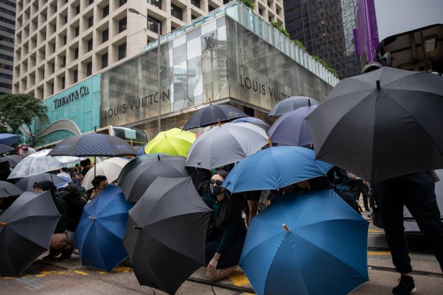 Protesters and office workers shelter behind umbrellas Tuesday as they demonstrate in Hong Kong's business district. Photo by Jerome Favre/EPA-EFE