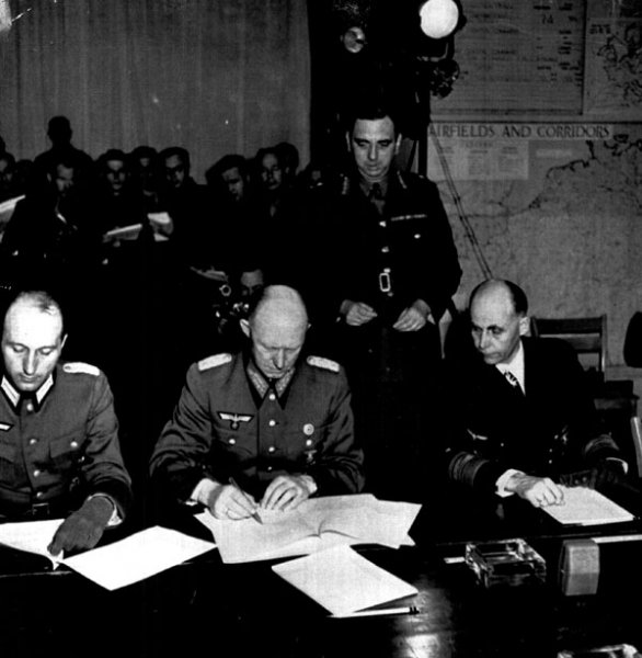Germany's Gen. Gustav Jodl signs the unconditional surrender documents on May 7, 1945 in Reims France ending the war in Europe. He is flanked by Col. Wilhelm Oxenius (L), his aide, and German Adm. Hans Georg von Friedeburg. File photo by UPI