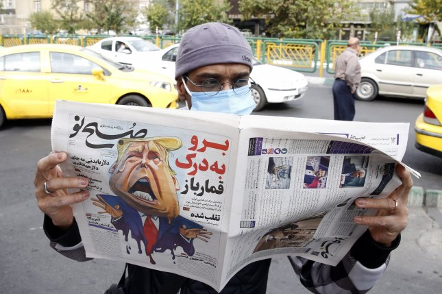 A man reads a copy of Iranian daily newspaper Sobhe Nou with a cartoon depicting U.S. President Donald J. Trump in front of a newsstand in Tehran, Iran on Saturday. Photo by Abedin Taherkenareh/EPA-EFE