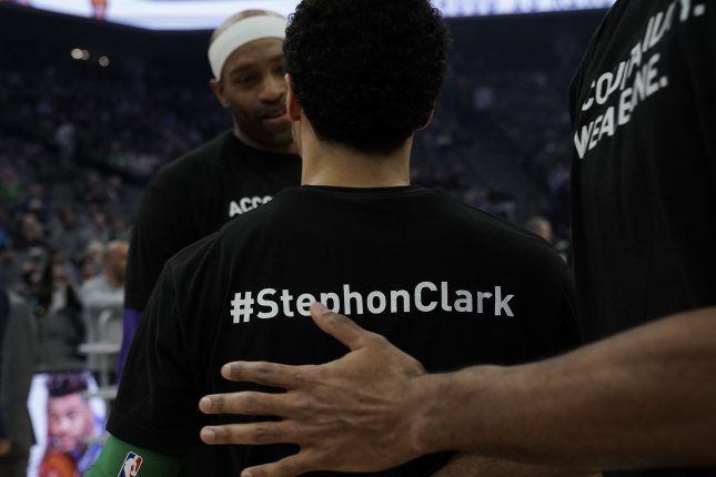 Sacramento Kings guard Vince Carter (L) talks with players with the Boston Celtics before their NBA game in Sacramento, Calif., on March 25, 2018. Both teams wore warm-up shirts in remembrance of unarmed Stephon Clark who was fatally shot by Sacramento police one week earlier. File photo by John G. Mabanglo/EPA