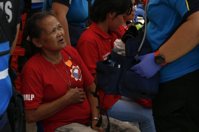 A Filipino supporter of former Philippine first lady Imelda Marcos puts her hand over her stomach after exhibiting possible symptoms of food poisoning outside the Ynares Sports Arena in Pasig City, east of Manila, Philippines, on Wednesday. Photo by Rolex Dela Pena/EPA-EFE