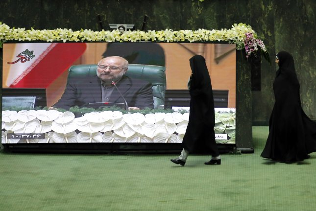 Iranian lawmakers walk past a screen displaying Mohamad Bagher Ghalibaf after being elected as parliament speaker at the Iranian parliament in Tehran. Only 6% of members of parliament are women. File Photo by Abedin Taherkenareh/EPA-EFE