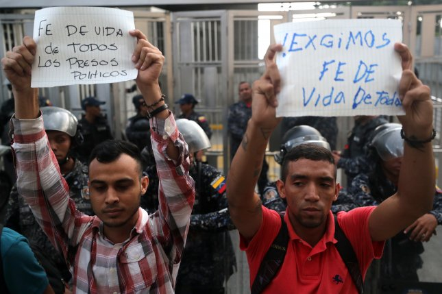 Supporters of imprisoned Venezuelan opponents hold signs during a protest in front of the Intelligence Service building. Photo by Miguel Gutierrez/EPA/EFE