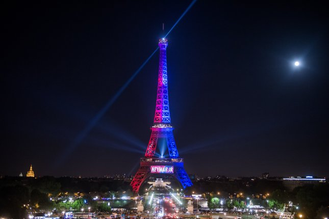 Paris' Eiffel Tower is illuminated in red and blue -- the colors of the Paris Saint-Germain soccer team -- on Saturday to celebrate the signing of the Brazilian star Neymar da Silva Santos Jr. At about 11:30 p.m. Saturday, a man trying to enter the Eiffel Tower in Paris with a knife was arrested. Photo by Christophe Petit Tesson/EPA
