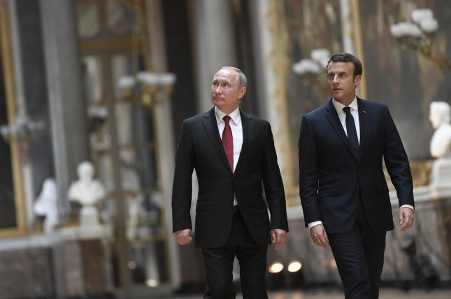 Russian President Vladimir Putin (L) and French President Emmanuel Macron (R) arrive for a joint news conference after their recent meeting at the Versailles Palace in Paris. Photo by Stephane De Sakutin/EPA/Pool