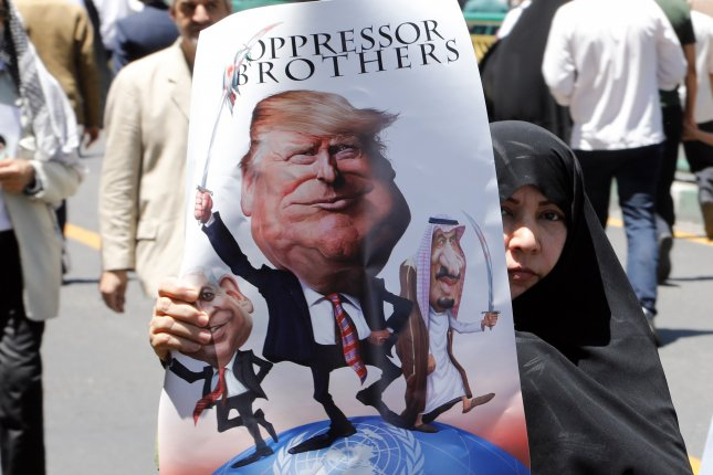 An Iranian woman holds a cartoon of U.S. President Donald trump standing between Israeli Prime Minister Benjamin Netanyahu and King Salman of Saudi Arabia during a rally in Tehran, Iran, on June 23. File Photo by Abedin Taherkenareh/EPA