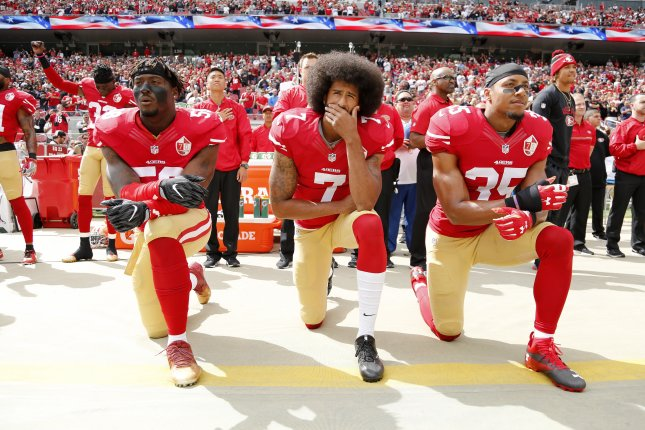 Former San Francisco 49ers quarterback Colin Kaepernick (C), outside linebacker Eli Harold (L), and free safety Eric Reid (R) take a knee during the national anthem before facing the Dallas Cowboys at Levi's Stadium in Santa Clara, Calif. File photo by John Mabanglo/EPA