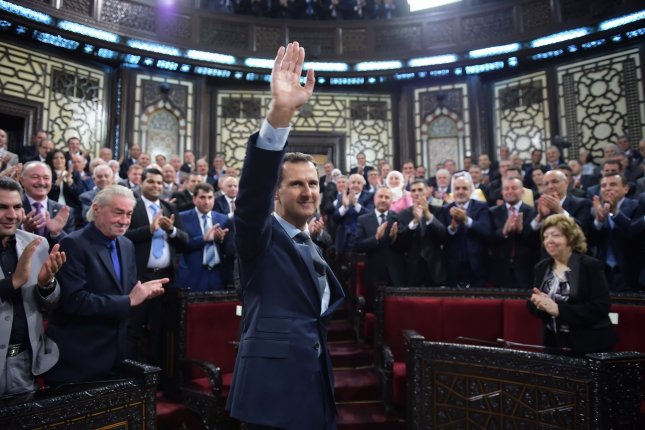 Syrian President Bashar Assad waves after speaking to the Syrian parliament in Damascus on June 6, 2016. According to new research, the majority of Americans favor the U.S. military helping to fight the Islamic State militant group in Syria with airstrikes and special operations forces, but largely do not support Pentagon efforts to aid rebels in their ongoing efforts to remove Assad from power. File Photo by SANA/UPI