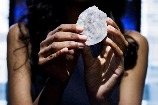 A model holds up the 1109-carat Lesedi la Rona diamond, reportedly the largest gem-quality rough diamond to be discovered in more than 100 years, during an auction preview at Sotheby's auction house in New York on May 4, 2016. The diamond was sold by Lucara Diamond to Graff for about $54 million. File Photo by Justin Lane/EPA-EFE