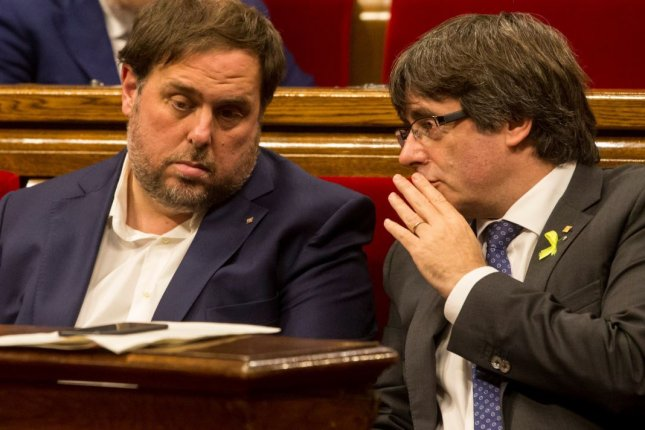 Catalan President Carles Puigdemont, R, talks with vice president Oriol Junqueros, L, on Oct. 27 in Catalan parliament in Barcelona. Speaking in Brussels on Tuesday, Puigdemont said he was in Belgium to make Catalonia's case to the European Union and is not in search of asylum. Photo by Enrique Garcia/EPA-EFE