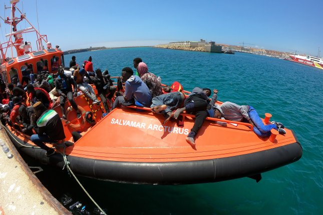 Rescued migrants rest on a Spanish Maritime Rescue services boat upon its arrival Friday at the port of Tarifa, Spain. There has been a 50 percent increase in migrant arrivals in Spain so far this year, compared to the same time period in 2017, the U.N. migration agency said. Photo by Carrasco Ragel/EPA-EFE