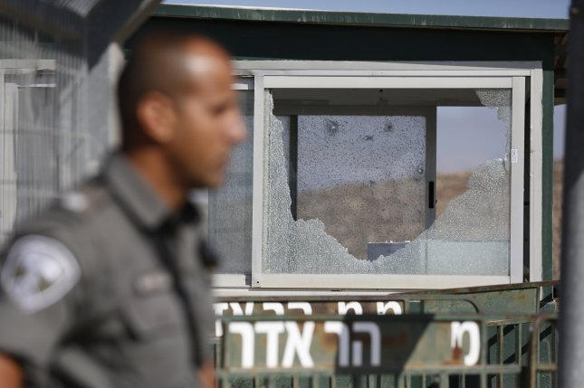 A police officer stands guard next to a broken window on the scene of a shooting attack at the entrance to the Jewish settlement of Har Adar, near Jerusalem, in the West Bank on Tuesday. Photo by Abir Sultan/EPA-EFE