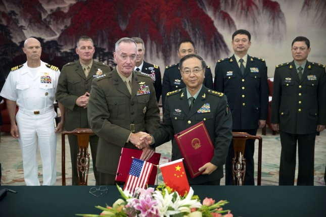 Marines Gen. Joseph Dunford (L), chairman of U.S. Joint Chiefs of Staff, and Army Gen. Fang Fenghui, chief of the General Staff of the Chinese People's Liberation, shake hands after signing a communications agreement in Beijing, China. Photo by Mark Schiefelbein/pool/EPA