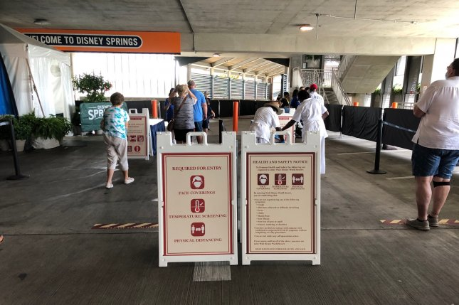 Masks, signs and temperature checks are required at Disney World's Disney Springs in July. Disney plans to lay off about 28,000 people across all its parks worldwide due to pandemic-related closures. File Photo by Paul Brinkmann/UPI