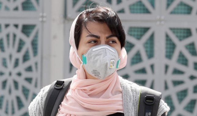 An Iranian woman wearing a face mask walks in Tehran, Iran, on Monday as the country faces a deepening COVID-19 epidemic. Photo by Abedin Taherkenareh/EPA-EFE