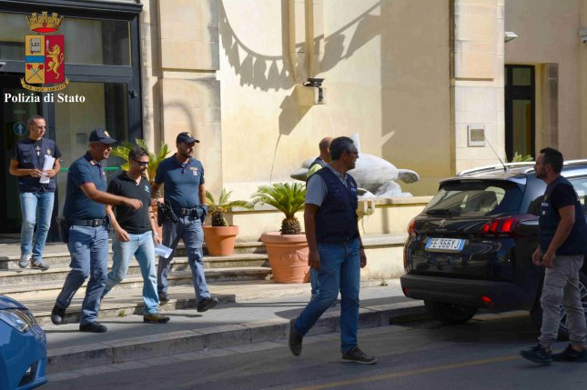 Italian police on Monday escort Davide De Vita (L-3), a firefighter arrested for allegedly starting fires and simulating rescue requests for money. Fifteen firefighters admitted involvement in the fraud in order to receive payment of about $12 an hour. Photo by State Police of Ragusa/Handout/EPA