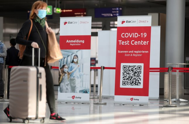 A passenger walks past a sign for the coronavirus test center at the Dusseldorf International Airport in Germany. File Photo by Friedemann Vogel/EPA-EFE/