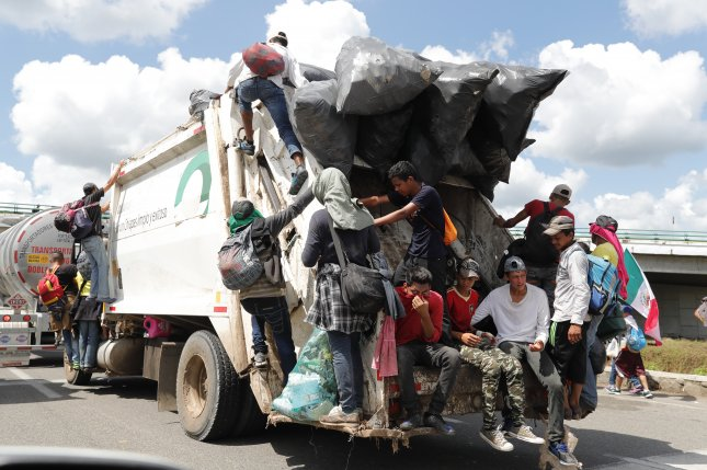 Honduran migrants climb on vehicles that are on the road as they continue on another stretch of Mexican territory towards the United States, after spending the night in Tapachula, Chiapas, Mexico, on Monday. Photo by José Méndez/EPA-EFE