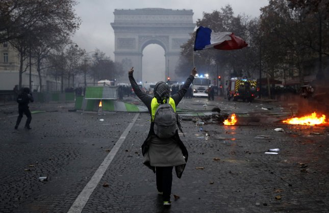 A protester wearing a yellow vest waves a French flag during clashes with riot police near the Arc de Triomphe as part of a demonstration over high fuel prices on the Champs-Elysees in Paris, France, Saturday. Photo by Yoan Valat/EPA-EFE