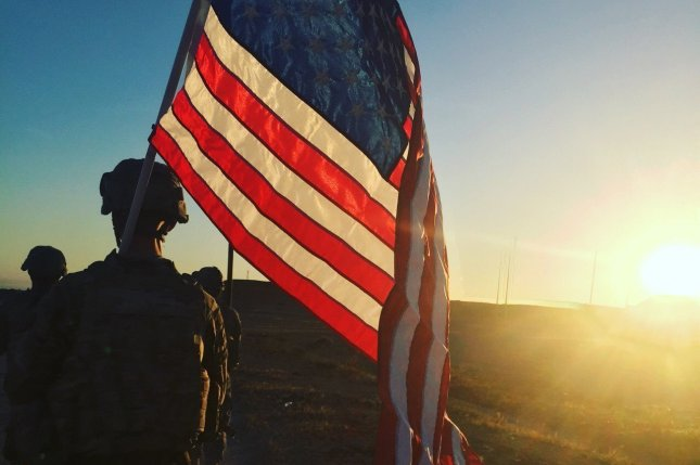 U.S. Army Sgt. Michael Swanker, assigned to the 1194th Engineer Company, 682d Engineer Battalion, carries the American Flag during the 25K Danish Contingency, or DANCON, ruck march at Al Asad Air Base, Iraq, May 3, 2016. Lt. David Bauders, of the 176th Engineer Company, died in what the Pentagon termed a non-combat related incident on May 6, 2016. Photo by Spc. Middleton/U.S. Army National Guard/UPI