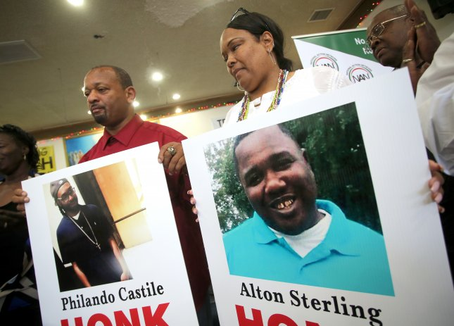 Demonstrators hold images of police shooting victims Alton Sterling, R, in Louisiana and Philando Castile, L, in Minnesota during a demonstration in Los Angeles on July 7, 2016. The family of Alton Sterling sued the city of Baton Rouge over Sterling's death on Wednesday. File photo by Mike Nelson/EPA