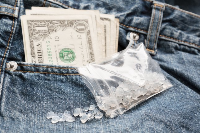 Crystal methamphetamine and cash money. Photo by Stepan Kapl/Shutterstock.com