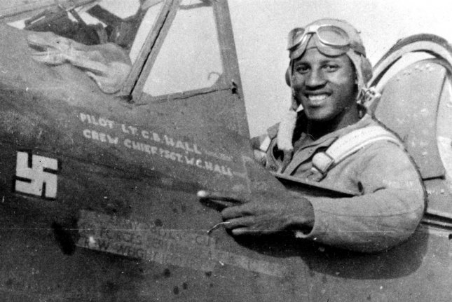 On July 2, 1943, Lt. Charles Hall became the first African-American pilot to shoot down a Nazi plane in World War II during an Allied assault on three Italian air bases. Seated in his P-40L Warhawk, Hall points to a freshly painted swastika marking his kill. File Photo courtesy of the U.S. Air Force
