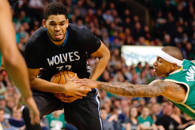 Former Boston Celtics guard Isaiah Thomas (R) reaches in on Minnesota Timberwolves center Karl-Anthony Towns (L) during the first half on March 15, 2017 at TD Garden in Boston, Massachusetts. File photo by CJ Gunther/EPA