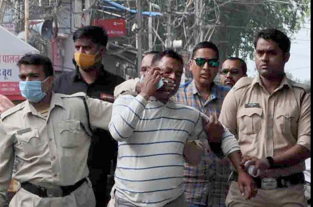Main suspect Vikas Dubey (C), the main suspect in the killing of eight police officers, was apprehended by Madhya Pradesh police on Thursday. The next day police fatally shot him when he tried to escape during a police transfer. Photo by Stringer/EPA-EFE