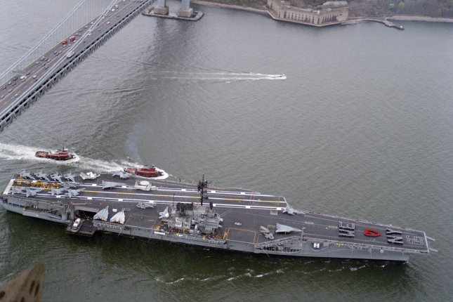 The aircraft carrier USS FORRESTAL (CV 59), escorted by a pair of tug boats, passes under the Verrazano Narrows Bridge as it approaches New York City for Fleet Week on April 29, 1989. (U.S. Navy)