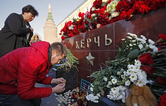 Mourners lay flowers on a monument in the Alexander Garden, Moscow, Russia, as a sign of mourning for the victims of the attack at a vocational school in Kerch in Crimea. A 20th person died Thursday, as authorities attempted to determine whether the shooter acted alone. Photo by Yuri Kochetkov/EPA