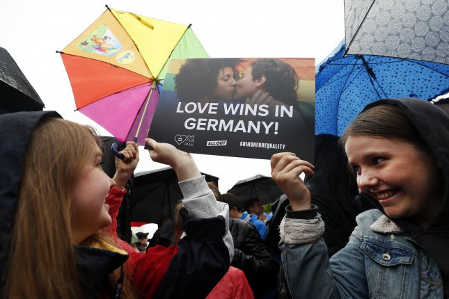 Two woman hold a placard reading Love wins in Germany as they celebrate outside the chancellery the approval of same-sex marriage by the German parliament Friday in Berlin. Photo by Felipe Trueba/EPA