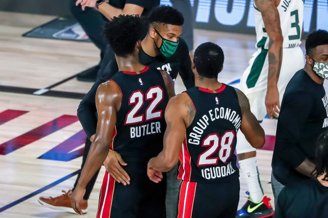 Injured Milwaukee Bucks star Giannis Antetokounmpo (C) greets Miami Heat forward Jimmy Butler (22) and Heat forward Andre Iguodala (28) at the conclusion of Game 5 in their Eastern Conference semifinal series Tuesday at the ESPN Wide World of Sports Complex near Orlando, Fla. Photo by Erik S. Lesser/EPA-EFE