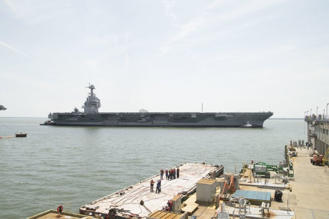 The USS Gerald R. Ford is pushed by tug boats as the ship enters Huntington Ingalls Newport News Shipbuilding to begin Post Shakedown Availability. Photo by Mass Communication Specialist 2nd Class Cat Campbell/U.S. Navy