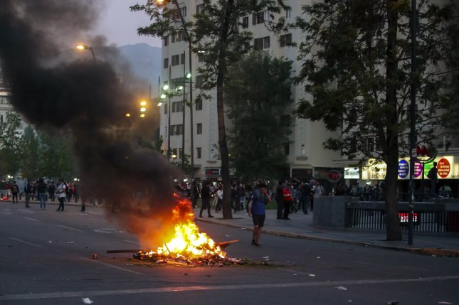 People demonstrate against the price rise of Metro tickets, in downtown Santiago, Chile, in October 2019. The protests against the Metro ticket price rise saw the closure of all suburban lines in the city. File Photo by Alberto Pena/EPA-EFE