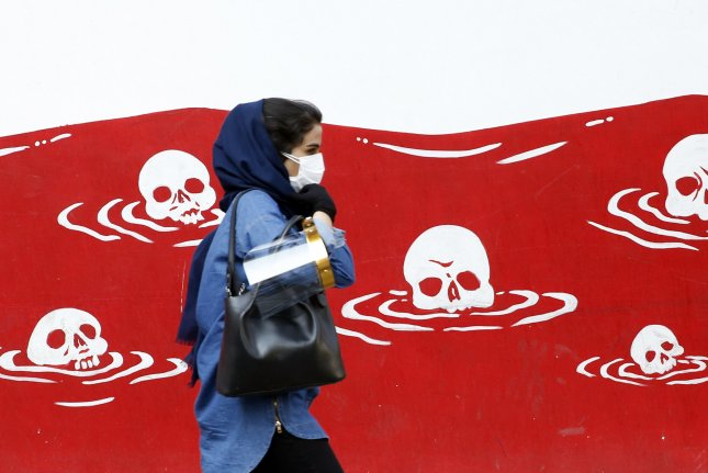 A woman walks past an anti-U.S. painting on the wall of the former U.S. Embassy in Tehran on Wednesday. Photo by Abedin Taherkenareh/EPA-EFE