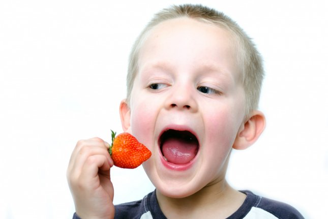 A boy eats a strawberry. Photo by George Hodan/Wikimedia Commons