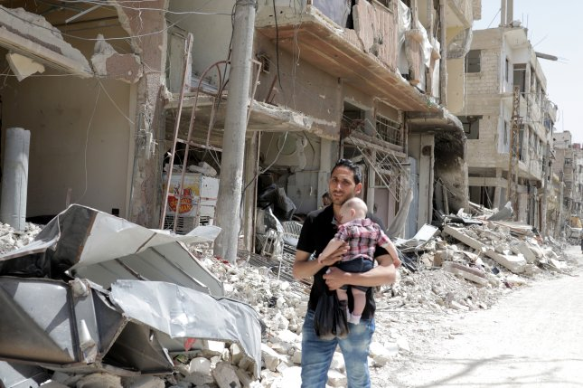 A Syrian man carries a young child amid the debris of bombed-out structures near Damascus, Syria. File Photo by Youssef Badawi/EPA-EFE