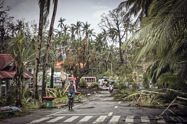 Citizens go past fallen trees and debris on the road due to effects of Typhoon Vongfong/Ambo in San Policarpo town, Eastern Samar province, Philippines, on Friday. Photo by Jerome Pedrosa/EPA-EFE