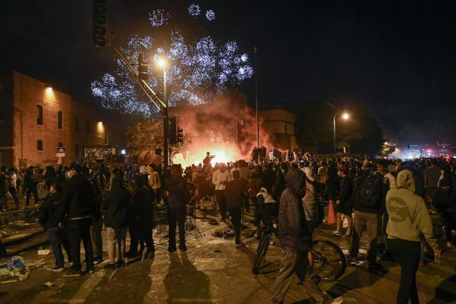 Protesters cheer as fireworks are lit and multiple fires burn Thursday night near an abandoned police precinct in Minneapolis as part of reaction to the death of George Floyd. Photo by Craig Lassig/EPA-EFE