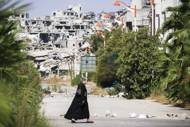 The Obama administration is considering a plan to strengthen military ties with Russia against Syrian terror groups in exchange for Russia getting the Assad regime to stop bombing U.S.-backed rebels. Pictured: A woman walks near a residential area in the city of Homs destroyed in the fighting between the rebels of the Syrian National Army. Photo by ART production/Shutterstock
