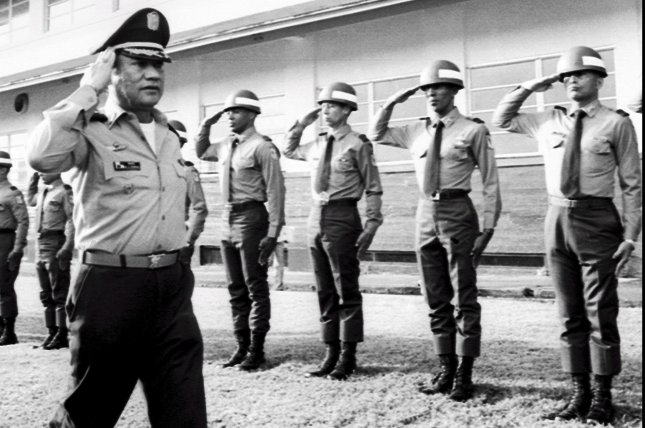 Former Panamanian dictator Manuel Antonio Noriega, left, walks by several of his troops in 1985. Family members said Tuesday that the 83-year-old former leader has undergone brain surgery to remove a tumor. Noriega ruled Panama between 1983 and 1989, when a U.S. invasion removed him from power. File Photo by STF/European Pressphoto Agency