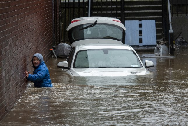 A boy wades towards a flooded alleyway in Pontypridd, South Wales, Britain, on Sunday after Storm Dennis brought torrential rains, floods and landslides throughout Britain. Photo by Neil Munnis/EPA-EFE