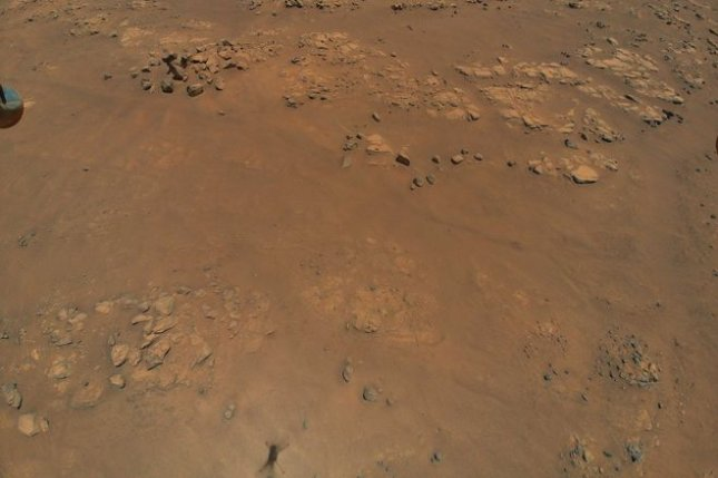 A photo taken by the Mars helicopter Ingenuity shows a rocky ridge and its shadow at the bottom. Photo courtesy of NASA