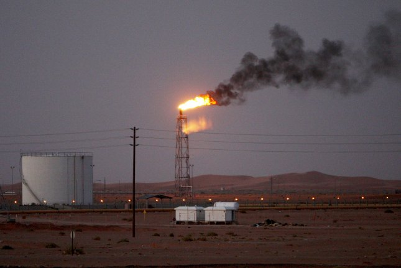 A gas flame is seen behind Saudi Aramco oil pipelines in the desert at Khurais oil field near Riyadh, Saudi Arabia. File Photo by Ali Haider/EPA-EFE